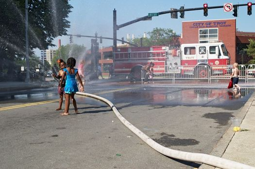 kids playing in fire hose water in Troy