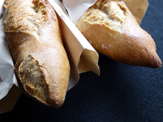 placid baker baguettes peeking out from bags