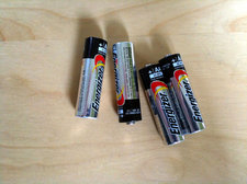 four AA alkaline batteries on desk