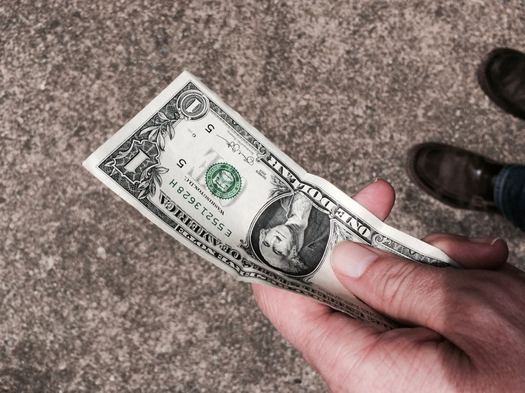 outstretched hand with dollar bill