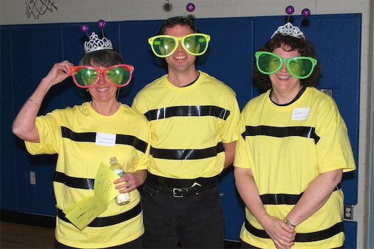 adults dressed in funny glasses and bee shirts