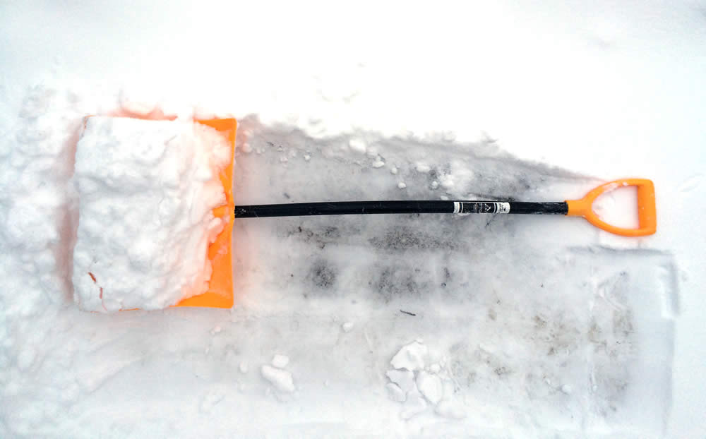 angled snow shovel in snow