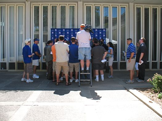 media huddled around coach at Giants camp