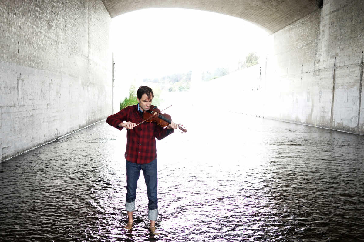 musician Andrew Bird playing violin in river