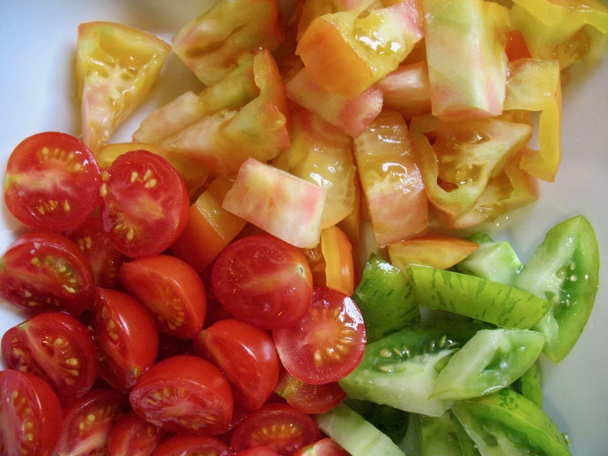 red and green and striped tomatoes cut up in bowl