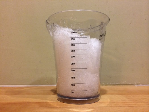 snow in a measuring cup