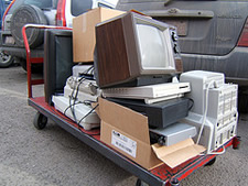 stack of old electronics on cart